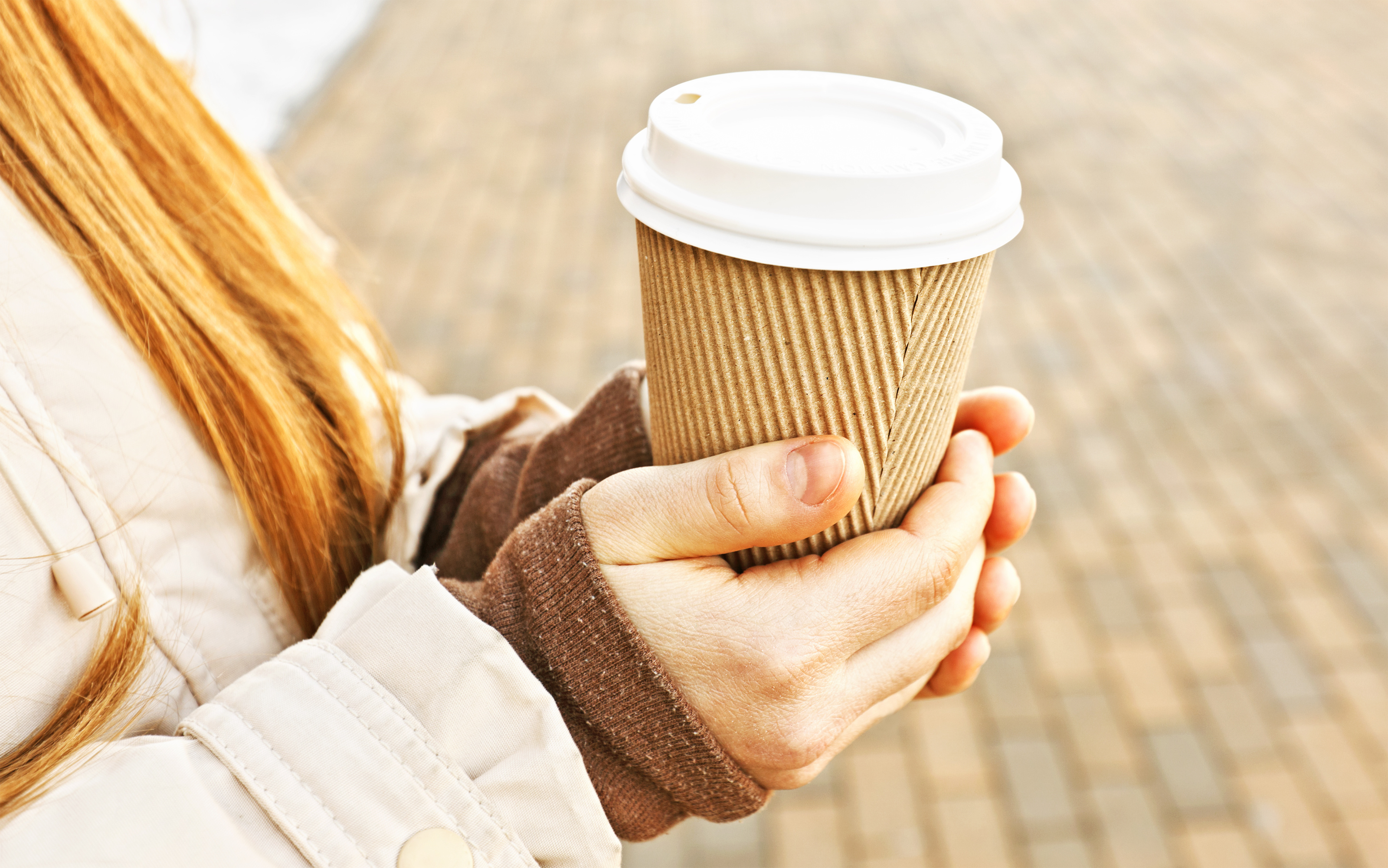 Woman hold cup of coffee on street